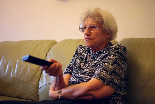 Woman with macular degeneration, watching TV