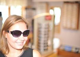 Woman trying on sunglasses in Laconia